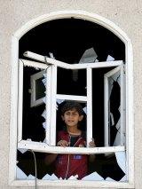 A boy looks through a window of his home damaged by an air strike near Sanaa Airport.