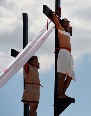 Reuben Enaje (right cross) playing the role of Jesus during the Passion Play a re-enactment of Christs crucifixion, on Good Friday.