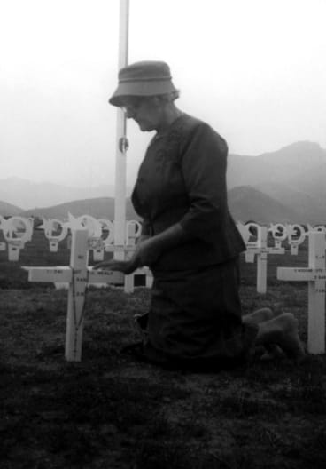 Bereaved Australian mother Thelma Healy kneeling at her son's war grave in Pusan, Korea,  in 1961.