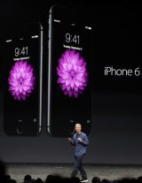 Apple chief executive Tim Cook showcasing the iPhone 6 and iPhone 6 Plus.
