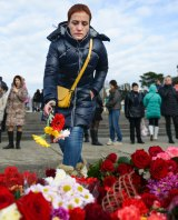 A woman lays flowers at a makeshift memorial at a pier in Sochi, Russia.
