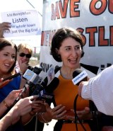 Minister for Transport and Minister for the Hunter Gladys Berejiklian is surrounded by activists while making a transport announcement in Newcastle.