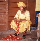 A woman in Sierra Leone with harvested fruits of Grains of Paradise.