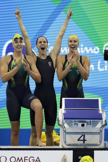 Australia's Emma McKeon, Brittany Elmslie and Bronte Campbell celebrate as Cate Campbell, bottom, finishes the women's 4x100-meter freestyle final setting a new world record.
