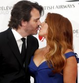 A kiss for good luck: Actress Poppy Montgomery kisses her husband Shawn Sanford on the red carpet.