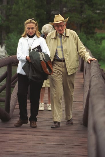 Hillary Clinton in 1995, carrying a copy of <i>Are We Alone: Philosophical Implications of the Discovery of Extraterrestrial life</i> by Paul Davies, with Laurence Rockefeller at the J.Y. Ranch in Jackson Hole, Wyoming.