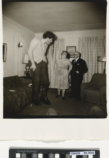 Diane Arbus, A Jewish giant at home with his parents in the Bronx, NY, 1970.