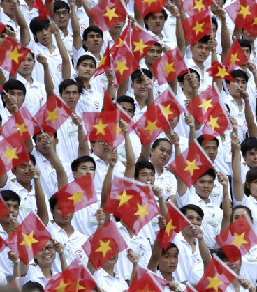 Performers wave Vietnamese national flags during a parade celebrating the 40th anniversary of the end of the Vietnam War.  Vietnam's economy is growing by around 6 per cent every year.