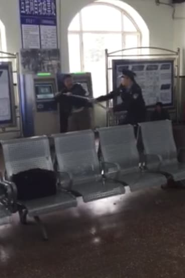 In this still image taken from cellphone video recorded on May 2 by a bystander, Xu Chunhe, left, struggles with policeman Li Lebin in a train station in Qing'an City.