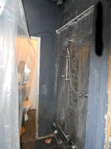 A makeshift shower in the hallway of an illegal housing set-up.