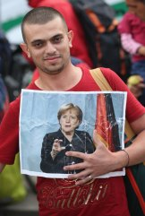 A migrant from Syria holds a picture of German Chancellor Angela Merkel.