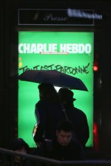 A billboard with the <i>Charlie Hebdo</i> cover in Paris.