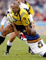 George Gregan attempts to tackle Jonah Lomu in Canberra in 2002.