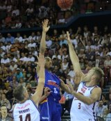 Terrance Ferguson floats a shot attempt over the defence of Brisbane forwards Daniel Kickert and Mitch Young.