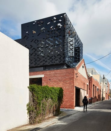 DKO Architecture retained the lower brick heritage building and added a lightweight laser-cut screen above.