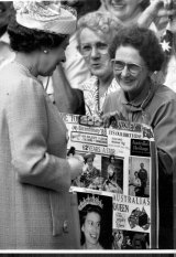The Queen looks over a paste-up of her early years during her walk through Darling Harbour, May 4, 1988.