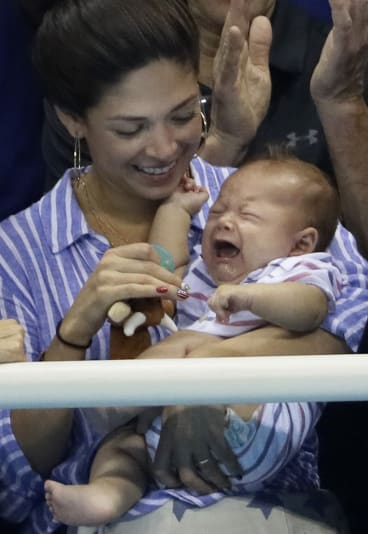 Phelps' fiancee, Nicole Johnson, with their son Boomer in the stands.