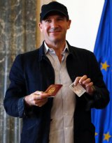 Ralph Fiennes poses for a photograph after receiving his Serbian passport.