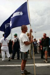 A man holds a Southern Cross flag at a rally at Webb Dock, Melbourne. April 8, 1998