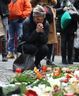 People lay flowers near where a lorry ploughed through a Christmas market in Berlin.