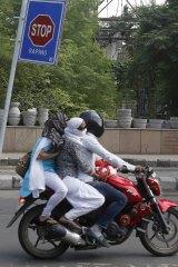 Commuters ride past an anti-rape sign in New Delhi.