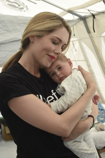 Tara Moss gives eight-month-old Nour a cuddle after she receives her oral polio vaccine in a mobile health clinic that visits each informal refugee settlement just once a month.