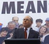 John Howard stands next to a 'cheaper diesel means cheaper goods' sign.