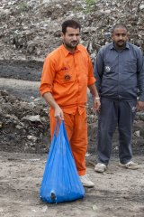 A Pakistani municipal worker carries a bag with dead rats to bury in the main garbage dump in Peshawar.