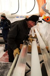 Dr Mark Curran examines an ice core inside the tent at the Aurora Basin North campsite.