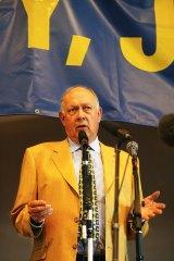 John Valder speaks to a packed hall of anti-John Howard campaigners.