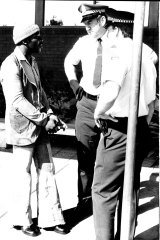 Clem Curtis (left) was taken in handcuffs from a jet on a warrant from the NSW state police on an assault charge in 1975.