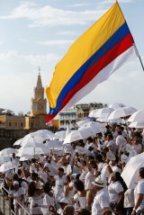 People wait for the start of the peace ceremony in Cartagena, Colombia on Monday.