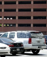 A demonstrators car is seen within the crime scene near the parking garage where Johnson died after writing the mysterious initials in blood.