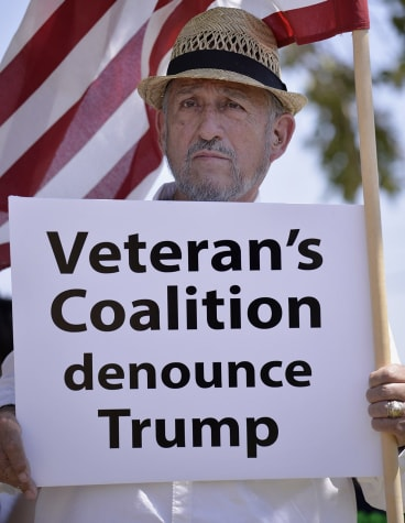Retired teacher Adolfo Gonzalez, a 39-year army veteran, holds a sign denouncing presidential candidate Donald Trump at Laredo International Airport.