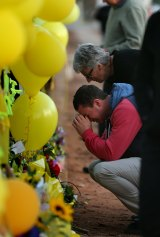 Stephanie Scott's mother Merrilyn Scott and her fiance Aaron Leeson-Woolley outside a makeshift memorial at Leeton High School shortly after the murder.