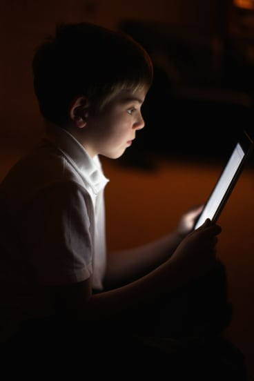Child reading on iPad.