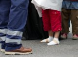 A refugee boy with bandaged feet stands beside an official after he arrived at the railway station in Munich, southern Germany.