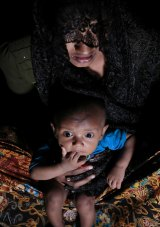 Mohsena Begum, a Rohingya who escaped to Bangladesh from Myanmar, holds her child at an unregistered refugee camp in Teknaf, near Cox's Bazar, in Bangladesh.