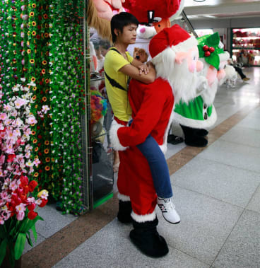 A man wearing a Santa Claus costume waits for customers outside of his stall at the Yiwu International Trade City.
