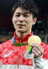 Japan's Kohei Uchimura displays his gold medal for the artistic gymnastics men's individual all-around final.