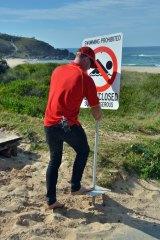"Duty surf lifesaver Ryan Rosenbaum erects a ""beach closed"" sign the day after the attack. Photo: Matt Attard/Port Macquarie News"