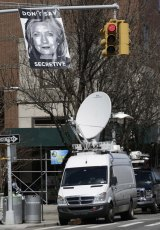 An unknown artist placed a poster on a traffic signal in front of the building where Hillary Rodham Clinton's presidential campaign offices are located.