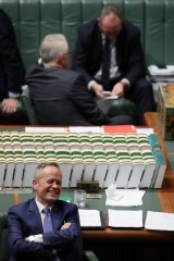 Opposition Leader Bill Shorten is all smiles in Parliament as Prime Minister Malcolm Turnbull and Deputy Prime Minister Barnaby Joyce talk during a vote.