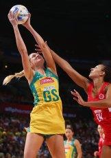 Caitlin Bassett of Australia stretches to take the ball ahead of England's Geva Mentor.