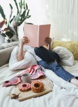 A comfy couch, doughnuts, coffee, and a book make this a pretty hyggelig nook.