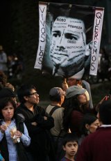 """Demonstrators in Mexico City hold a picture of President Enrique Pena Nieto bearing the slogan """"we want them alive""""."""
