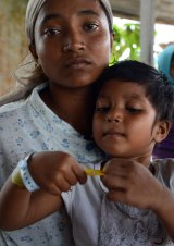 Mimi, a Rohingya mother from Myanmar and her daughter Asma rest at a confinement area in Langsa port, Aceh province.