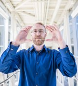 MSU researcher Richard Lunt holding the transparent solar panel.