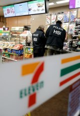 US Immigration and Customs Enforcement agents serve an employment audit notice at a 7-Eleven in Los Angeles.