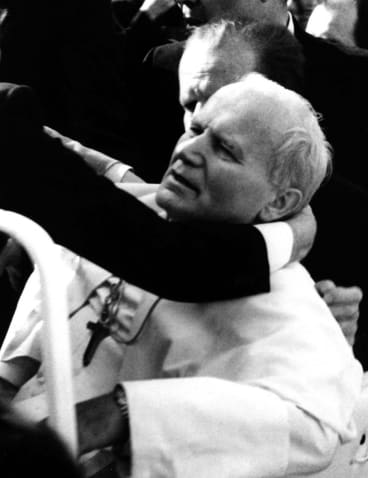 Pope John Paul II lies seriously wounded in his open car moments after he was shot by Mehmet Ali Agca in St Peter's Square on May 13, 1981.